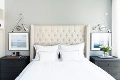 Bright and timeless bedroom with matching art, wall sconces, and bedside tables and white bedding with tufted headboard