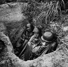 Muddy and drenched American infantryman Terry Moore (center) huddles with his buddies (all wearing ponchos), in a foxhole during intense sniper fire as they wait to advance on enemy positions on Okinawa, May 1945. (Photo by W. Eugene Smith//Time Life)