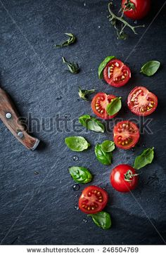 halved juicy cherry tomatoes and basil leaves on a black slate. cherry tomatoes and herbs on a black slate. concept for healthy nutrition. Vegetables Photography, Food Photography Tips, Knife Photography, Italian Recipes, New Recipes, Recipies, Food Flatlay, Basil Leaves, Tomato Basil