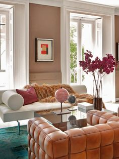 Fur + mirrored coffee table + leather club chairs + ethnic rug. Elle Decor Spain.