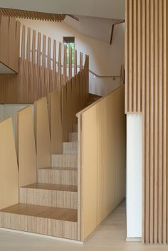 """<span style=""""line-height: 1.8;"""">A view of the central staircase from the entry-level floor emphasizes vertical, tapering forms, a motif found throughout the home.</span>"""