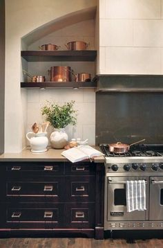 A collection of copper pots on open shelves draws attention to the dramatic stove in this upscale country kitchen designed by Nam Dang-Mitchell. Kitchen Stove, Kitchen And Bath, New Kitchen, Kitchen Dining, Kitchen Cabinets, Black Cabinets, Spanish Kitchen, Kitchen Black, Distressed Cabinets
