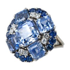 Platinum cocktail ring with a wonderful disc of mixed sapphires and diamonds. There are 5 lighter color square emerald cut sapphires radiating out from the center, with an edge of round darker blue sapphires. All the sapphires are natural. In between the two are 8 round brilliant cut diamonds. It is numbered and signed OSCAR HEYMAN.Circa 1950