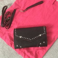 Black Clutch with Pink Piping Cutest black bag has pink piping and silver studs. Comes with wristlet and long strap. Inside has two sections separated by zipper compartment. Faux leather. Excellent condition. 8 1/2 x 5 1/2 Bags