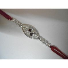 German-Silver-with-2red-stone stud in middle. Rakhi has an elegant shine. FREE tilak and a bar of chocolate is provided with it.