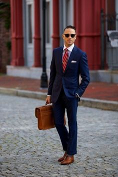 Men's Black Sunglasses, White Dress Shirt, White Pocket Square, Red Vertical Striped Tie, Navy Suit, Brown Leather Briefcase, and Brown Leather Brogues