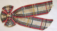 "1860-1870, ""Rosette"" - ribbon bow. Manchester City Galleries, 1987.2.  ""Tartan silk-satin. Central bow with two long pendant ends. Tartan composed of a wide central cream band flanked by narrow bands of (respectively) blue, black, yellow, black, green, red, black and red.    Checked with wi""dely spaced narrow bands of blue, cream, yellow, green and red."""