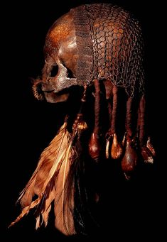 ASMAT TRIBE: HUMAN ANCESTOR SKULL #8  HAND CARVED BONE NOSE DECORATION,  HUMAN SKULL, BEADS, FIBER, FEATHERS, SHELL, CASSOWARY.  Asmat is located in the Province of Irian Jaya which is the western half of the island of New Guinea, the second largest island in the world.