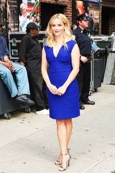 Reese Witherspoon wears a royal blue shift dress with metallic sandals