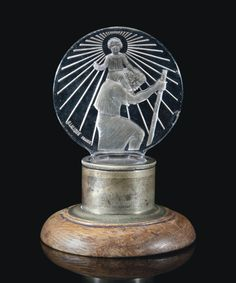 ST CHRISTOPHE MASCOT, NO. 1142 designed 1928, clear, frosted and sepia stained, with slight amethyst tint intaglio R. LALIQUE FRANCE (nicks) with Breves Galleries mount set in oak 18 cm. high including mount