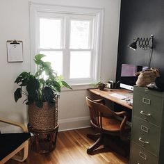Industrial inspired office with black accent wall, vintage wood chair and filing cabinet & plants