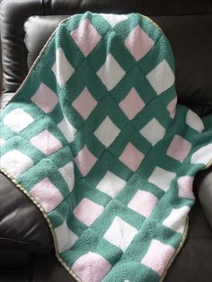 Knitted Mitre square blanket, backed with fabric and edged with ribbon