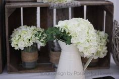 Country style wedding table centre jug with flowers and hydrangeas in jam jars with hessian