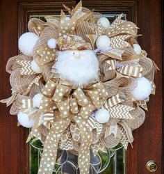 This 28 wreath is very full and whimsical with its burlap and white color theme! It features a natural Santa, burlap and white ribbon, burlap bow with white polka dots and white decorative snowballs! Two wreaths are available and would be perfect for double doors