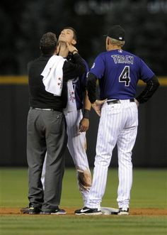Colorado Rockies' Tyler Colvin is checked out by a trainer as manager Jim Tracy (4) looks on after Colvin was accidentally kicked in the back of the head by Arizona Diamondbacks shortstop John McDonald during the first inning of a baseball game, Monday, Sept. 24, 2012, in Denver. (AP Photo/Jack Dempsey)