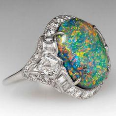 Deco-era opal and platinum halo ring via @eragemjewelry