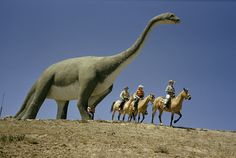 Tourists on horses ride past a life-size apatosaurus statue in a South Dakota dinosaur park, 1956.Photograph by Bates Littlehales, National Geographic
