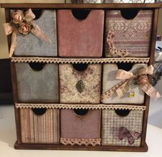 This beautiful mini chest of drawers is ready to store all of your treasures. It is hand made using quality papers and embellishments. The frame is made of wood and each drawer is made of thick chip board and covered with cardstock. It is hand sanded and inked. The lace and flowers are hand dyed. The chest measures about 9 ½ x 8 ½. The drawers measure about 2 x 2. This would be a perfect addition to any room.
