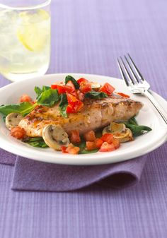 Baked Salmon with Tomatoes, Spinach & Mushrooms – In this Healthy Living recipe, flavorful salmon is baked with spinach, mushrooms and tomatoes and dressed with vinaigrette.
