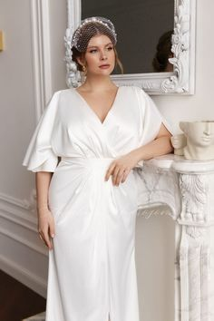 Plus size wedding dress by Dream&Dress. Half sleeves satin bridal gown, church winter wedding. The A-line light dress is for brides seeking self-expression, riveting beauty, subtle sexiness, and sensuality. Soft and feminine silhouette, a slit skirt, a V-neckline, airy half sleeves, and an original draping make this dress extremely charming and stylish at the same time #weddingdress #rusticwedding
