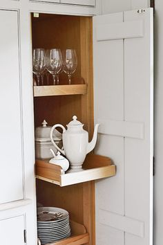 This tall cabinet with maple doors and board-and-batten detail on the inside, conceal occasional-use serving pieces and wine glasses on slide-out shelves.
