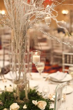 tall centerpieces wth silver branches, hanging votives, sitting in winter green wreath with white roses and little pinecones in it
