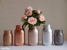 ***PROCESSING TIME IS 3 WEEKS BEFORE SHIPMENT. SHIPPING TAKES 2-3 DAYS FOR US STATES *** These beautiful metallic painted mason jars are ideal for wedding centerpieces or home decor. They are painted on the outside only, so can hold fresh flowers and water. METALLIC PAINTED JARS MUST BE HANDLED WITH CARE. PLEASE TRY TO HOLD JAR FROM INSIDE RIM. This listing is for 5 jars. 3 quart size jars (6 3/4 tall) and 2 pint size jars (5 tall). Jars come with lids. The colors are classic rose gol...