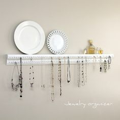 Jewelry holder made from molding and tacks.