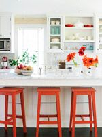 Small kitchen. Lots of light, light colors, pops of poppy red, open cabinets, stools at 'breakfast bar'
