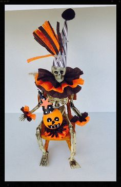 Halloween decoration  A six inch skeleton is wearing a crazy party hat and a fluffy crepe paper collar and matching cuffs He is sittingin a dollhouse chair and has a handmade jack o lantern sitting in his lap. Colors are traditional orange and black but not coming out right with camera.   Can sit or hang  comes with a twine loop for hanging.  Halloween ornament