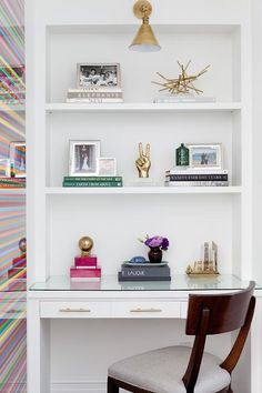 chic home office features a wall clad in thibaut ikat wallpaper lined with a wall to wall floating shelf accented with art from minted chic home office features
