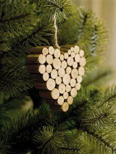 Los adornos de madera siempre crean ambientes cálidos y acogedores porque nos remiten a la montaña y a Navidades envueltas en nieve. adornos de madera como este corazón de troncos
