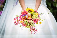 Bruidsboeket in kleurrijke multi-color tinten met oranjerode en roze rozen, paarse campanula's, gele zonnebloem, roze gloriosa lelies, afgewerkt met oranje en zachtgroene accenten.