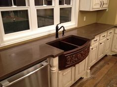 these concrete counter tops are beautiful.  The white cabinets with the brown is awesome.  They back splash here isn't yet installed.