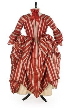 A fine striped robe à la polonaise, French, 1770s. of cinnamon and ivory satin stripes, with double engageants, English back, the interior with tapes and loops to form polonaise folds; with ivory satin stomacher covered with pinked ribbon rosettes; and a finely quilted ivory satin petticoat with overall lattice design and flowerheads within triangles to the hem. (back)