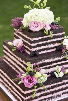 This is not just a naked wedding cake but a chocolate and raspberry wedding cake, with simple, uniform layers and delicate pink flowers. By Cassidy Budge Cake Design