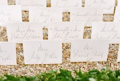 These calligraphed seating cards sit in gravel at a country estate wedding.