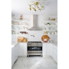 All white kitchen with mixed materials such as marble floor, tiles backsplash, and stainless steel. #rumahkukitchen
