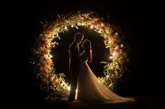 """This couple had a custom-built, floral-framed circular arch as part of their Belarus wedding ceremony. During the day, the flowers provided a beautiful pop of color as the bride and groom took their vows, and at the nighttime reception, the arch was filled with lights. """"After the ceremony and fireworks, I asked the couple to stand by the arch for a couple of minutes to get a romantic portrait,"""" says photographer Sergey @lapkovsky. """"I knew that I wanted to create an image like this the moment…"""