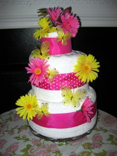 "Towel ""Cake"" - Wedding Shower Gift.    I made this recently for a friend's wedding shower.  It was made with items on her registry:  two bathsheets, two towels, two washcloths and three serving utinsiles.  After the flowers, ribbon and butterflies were added I wrapped the ""cake"" with clear cellophane gift wrap, gathered it at the top with coordinating ribbon, and presented it on a cakestand on the gift table."
