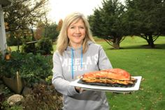 """Cookbook author Tiffany Haugen lives in Walterville with her husband, co-author Scott Haugen, and their two sons. Here, she holds Cedar Planked Salmon, which is prepared on a bed of citrus slices. The Haugens' latest cookbook, """"Cooking Seafood,"""" is for cooks of all skill levels. """"I want people who go get their fish from a fish market to be able to use this book,"""" Haugen says. (Collin Andrew/The Register-Guard)"""