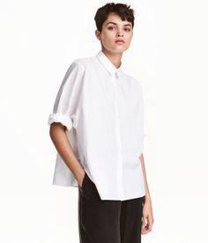 Wit. PREMIUM QUALITY. Een wijde overhemdblouse van premium cotton met een smalle…