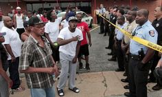 A crowd is stopped by police from reaching the scene where Michael Brown, 18, was fatally shot by police in Ferguson, Missouri, on Saturday. Photograph: Huy Mach/AP  Associated Press in Ferguson, Missouri      theguardian.com, Sunday 10 August 2014 13.55 EDT
