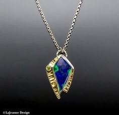 Cosmopolitan - Azurite/Malachite with Peridot, 18K Gold Sterling Silver Necklace  This necklace features a dark blue Azurite/Malachite stone. It is accented on the side with a faceted green Peridot gemstone. For added bling is a layer of stamped,18K gold on the sides of the stone. The pendant hangs on an 18-inch sterling silver rolo chain.  The back has been stamped with the .925 hallmark and makers mark.  Pendant measures 1-1/2 inches (38mm) from top to bottom and 7/8-inc...
