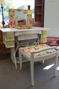 "This is an old sewing table turned into a vanity for doing hair and make-up! I painted the base and main frame in white and green. I covered the chair in a floral fabric.  I also used the same fabric to line the drawers, lid and sunken hole where the sewing machine would normally go.  You can buy this iron on ""vinyl"" to turn any fabric into vinyl, so I used that on the liners so they could easily be wiped out.  I then placed a mirror on the lid using screws and plastic holders. Voila!"