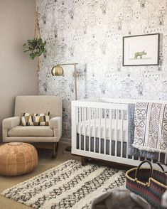 gender neutral nursery. white crib, wallpaper wall, hanging plant and white and black rug