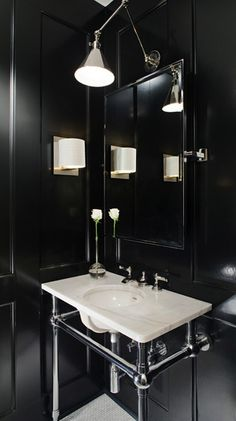 Amazing powder room with glossy black wood paneled walls, 2 leg marble washstand, rectangular pivot mirror, small marble tiles floor and Ralph Lauren Anette Library Light in Polished Nickel.