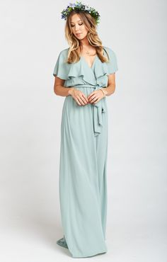 The Audrey Maxi Dress is the epitome of classic beauty while being current and chic. Her crossover ruffle gives a bit of a flutter and the appearance of a wrap but with the security of a elastic waist. Includes a matching detachable sash to hide that little waist if you please. *MADE IN THE GORGE USA* *100% Poly *Detachable waist tie sash *Lined as a mini dress *Wrap around skirt creates slit *Appearance of a wrap, waist is elastic *Mumu Bridesmaid dresses are standard 'long'...