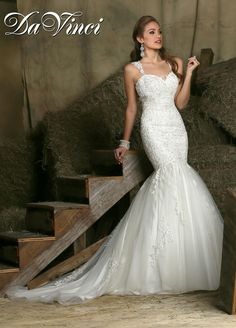 """DaVinci Style 50330 is a lace and tulle mermaid wedding dress with plenty of style and drama. This gorgeous lace mermaid is one of the many sweetheart wedding dresses in our Fall 2015 line and features an elegant, fitted, beaded lace bodice. Thefull tulle """"mermaid's tail"""" skirt has delicate lace appliques and a long, semi-cathedral train. It is also one of our more unique wedding dresses, with straps, a high-neck, lace illusion back and a long string of buttons. Comes in ivory or white."""