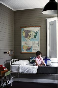 Photography Sharyn Cairns Styling Geraldine Munoz Little boys room. Putty walls, industrial light, iron bed, vintage map.